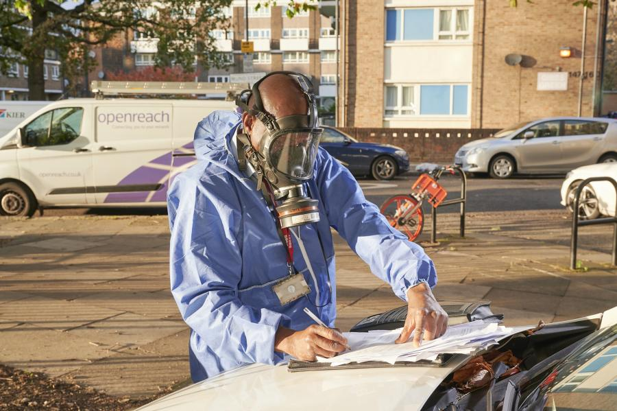 Pest control crew member filling in some paperwork on a vehicle bonnet