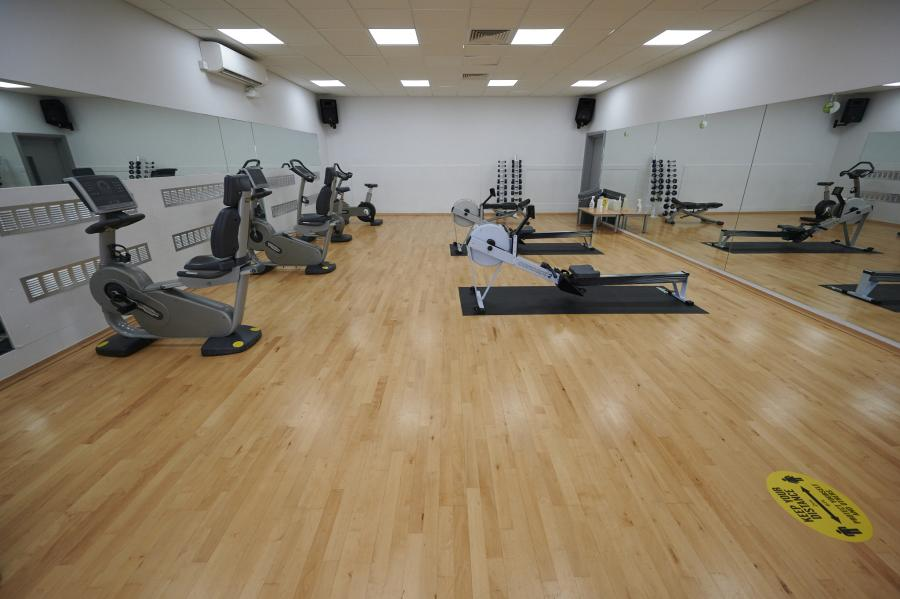 Empty gym with fitness equipment in place and clean wooden flooring