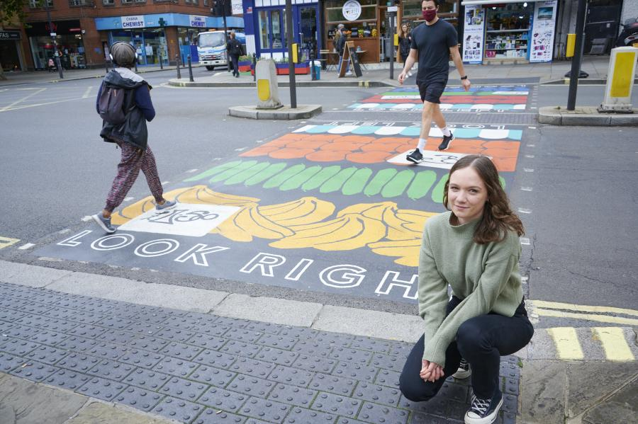 Artist Henri Holz kneeling by the North End Road rainbow crossing she created