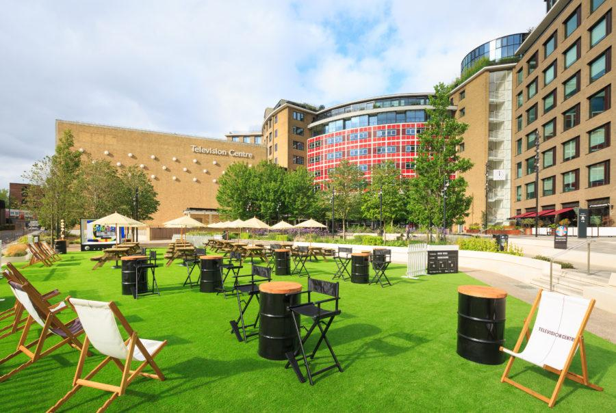 Artificial grass, tables and chairs with the Television Centre in the background