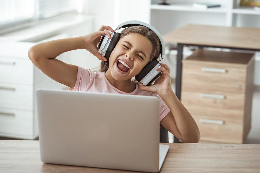 Girl wearing headphones listening to music on a laptop computer
