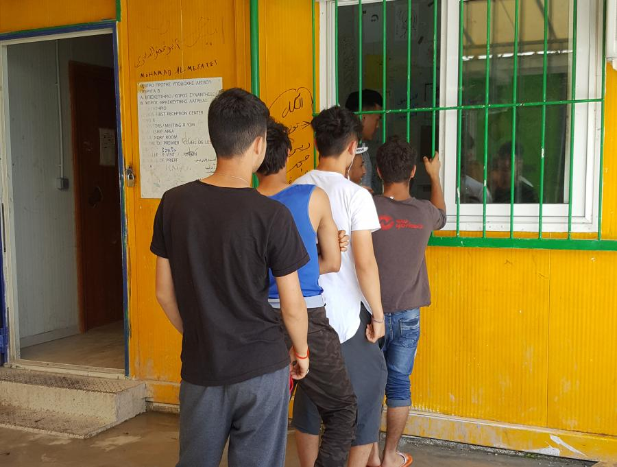 Children in a line queuing in line for food at a window covered by green metal bars