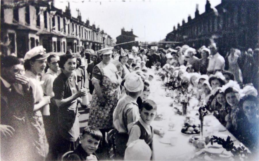 Group of residents standing and sitting at a street table on Carthew Road