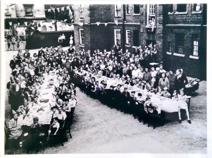 Children sat around two tables in the courtyard of the Lewis Trust Buildings in Lisgar Terrace