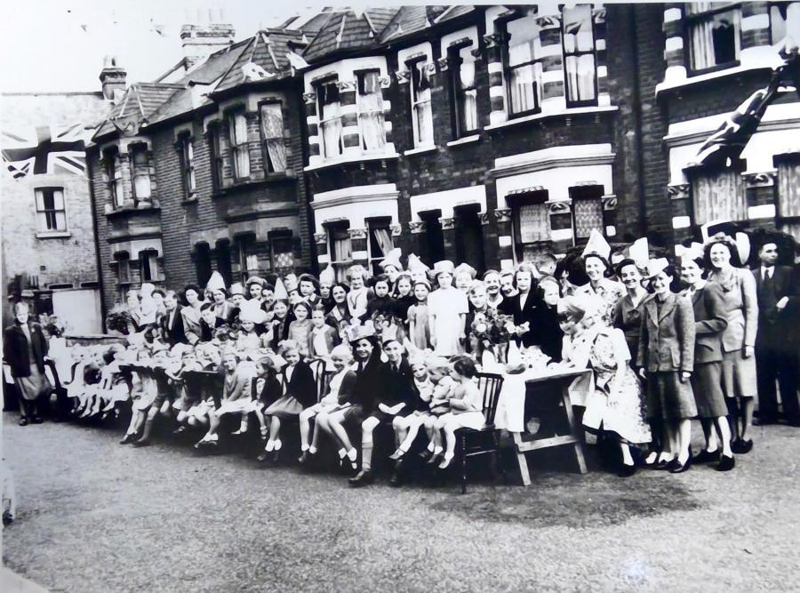 Residents and children sat around a table celebrating VE Day in 1945