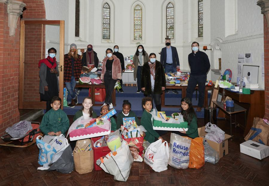 Wendell Park pupils, staff and members of the church community inside St Saviour's Church with shopping bags filled with contents for the hampers