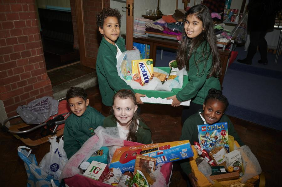 Group of children in Wendell Park primary uniform sat on the floor holding Christmas hampers