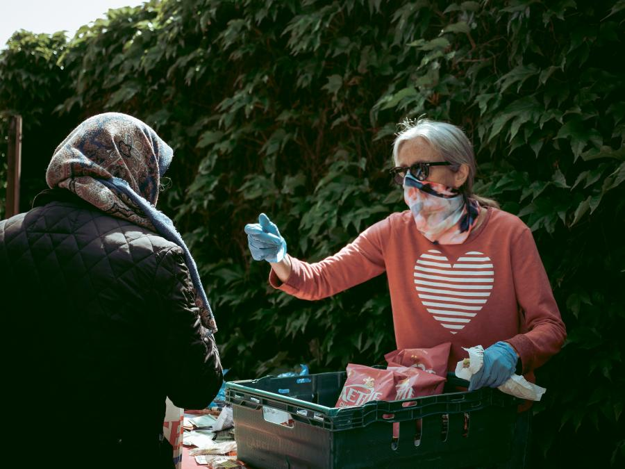 Volunteer handing out food supplies from a green plastic container
