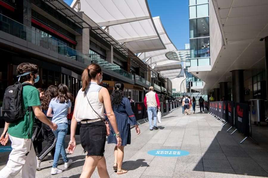 Shoppers walking along a pedestrianised avenue at Westfield London in White City