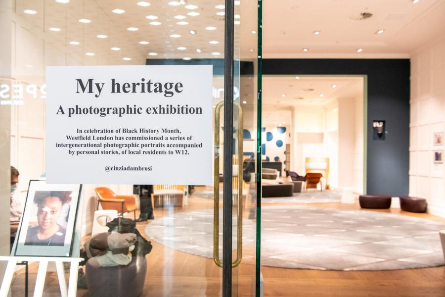 Glass window of the exhibition space with a sign and photographs on the wall in the background