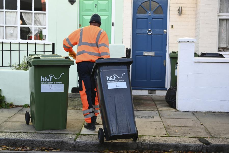 Worker pulling two wheeled bins across the pavement