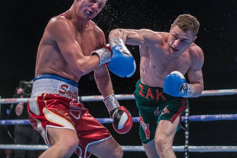 Zak Chelli landing a right punch on Jimmy Smith