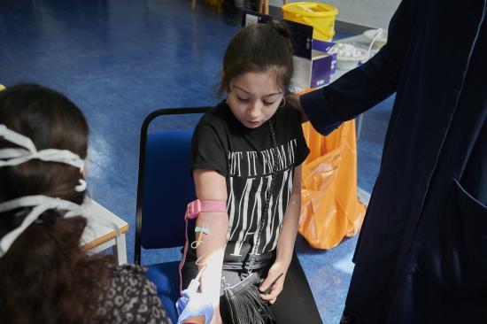 Child sat in a chair receiving a coronavirus test