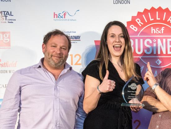 Charlie Raworth and Lara Coker-Hutchins on stage picking up an award