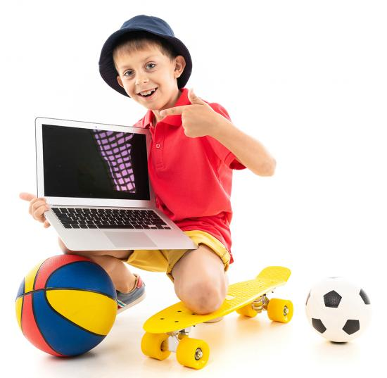 Child playing on the floor with balls, skateboard and a laptop computer