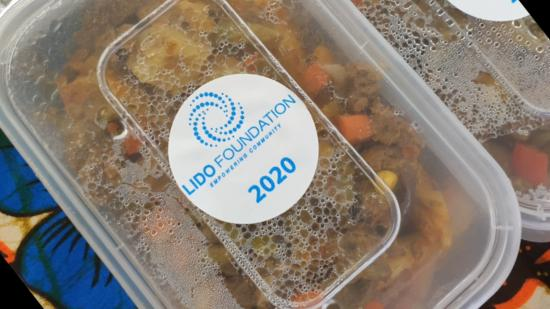 Plastic container containing cultural food with Lido Foundation branding on the lid