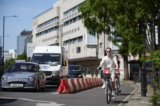 Cyclist riding outside London Olympia behind a temporary safety barrier