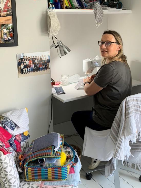 Dorothée d'Argentré working at her desk on her sewing machine