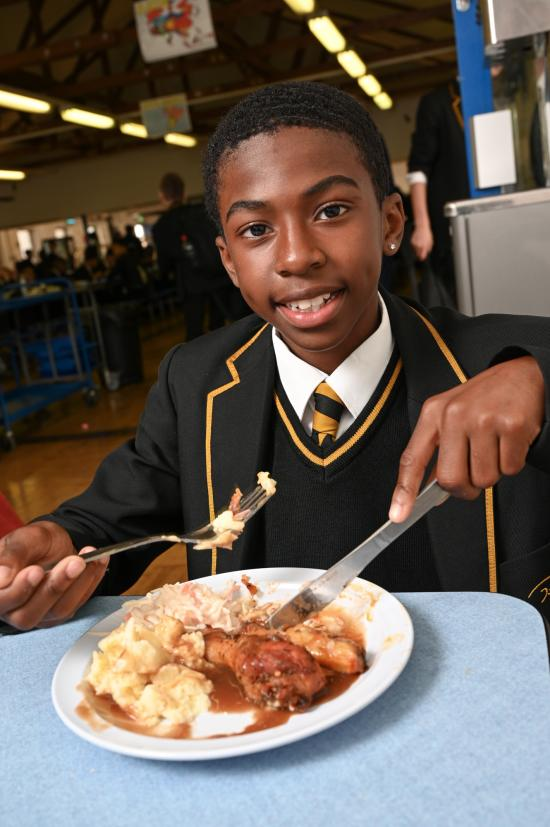 Boy eating a meal at school from a tray