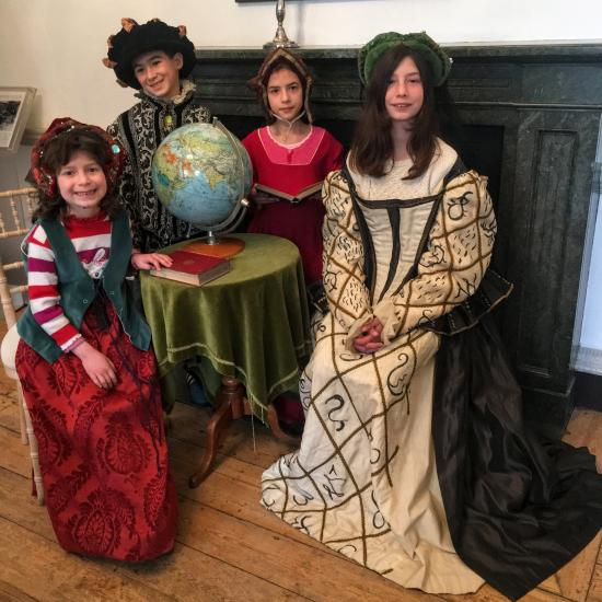Children dressed up in Tudor costumes enjoying a themed day out at Fulham Palace