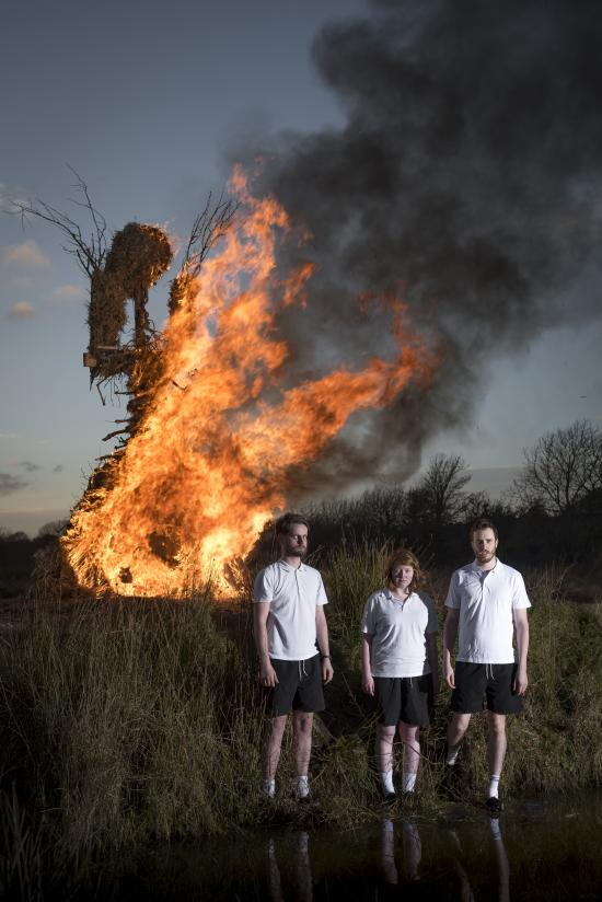 Burning effigy in the background and three people dressed in primary school PE kits in foreground standing by lake