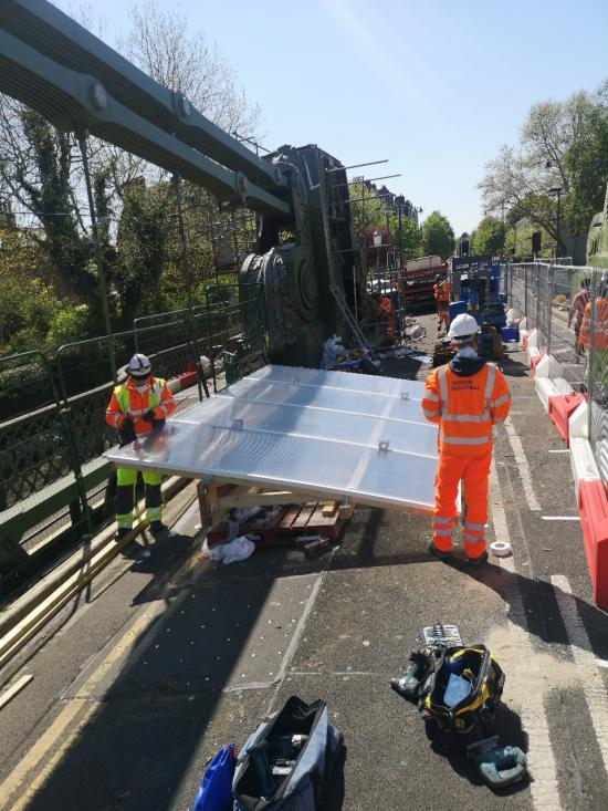 Workmen standing on Hammersmith Bridge in safety gear dealing with attaching a new roofing structure to a crane