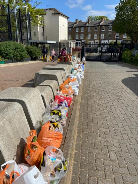 Food in carrier bags on the kerbside at Hammersmith Academy awaiting distribution