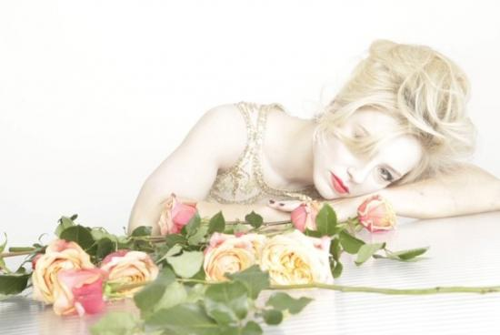 Harriet Stubbs leaning across a a table top with roses in the foreground