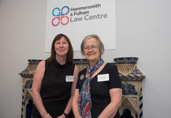Two staff from the Hammersmith & Fulham Law Centre standing in front of their corporate sign