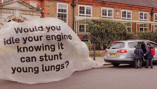 Image of a car with 2 children outside a school. The car's exhaust pipe is inflating a huge bag with it's exhaust fumes. There is a message on the bag saying 'Would you idle your engine knowing it can stunt young lungs?'
