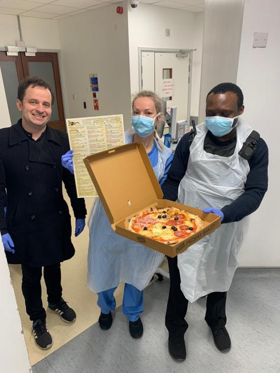 Man and two Charing Cross Hospital medical staff holding an open pizza box