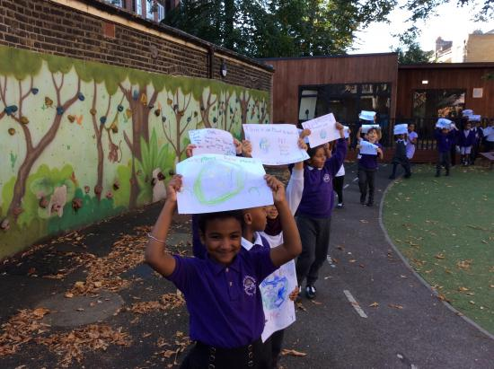 Pupils from Miles Coverdale Primary School in the playground with climate change banners