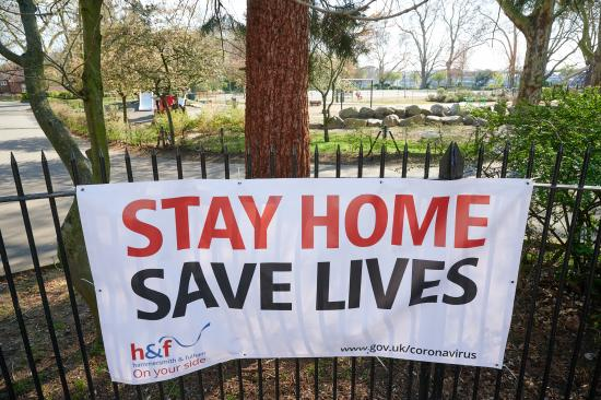 Stay Home Save Lives banner attached to fence outside a park
