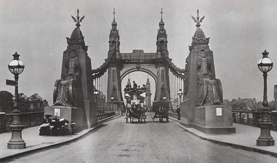 Black and white photo of a horse and cart crossing Hammersmith Bridge