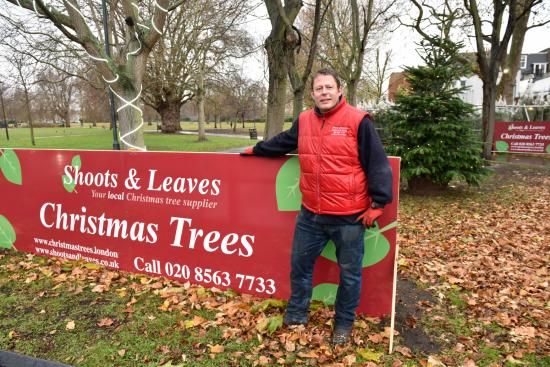 Hew Stevenson stood next to a red promotional banner for his business in a park