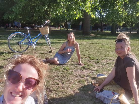 Three women sitting on the grass in a park
