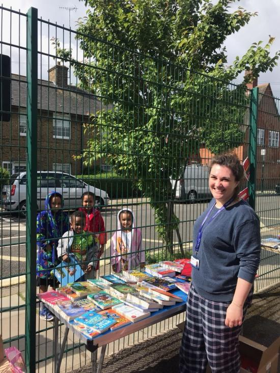 Teacher behind a table heavy with books in the Old Oak primary school playground