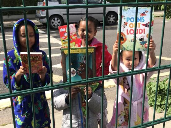 Four children stood outside their school railings holding books in their hands