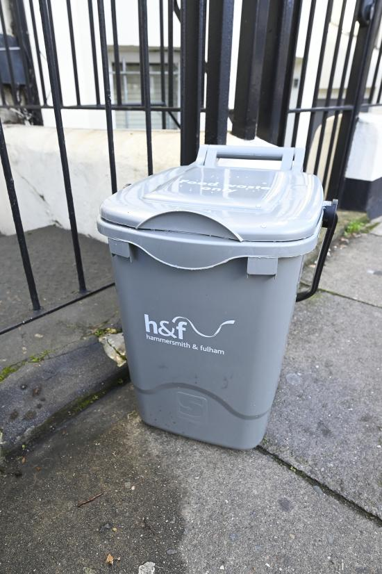 Outdoor food waste caddy stood on the pavement in front of some black railings