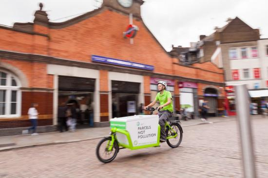 E-cargobike and rider moving along the road in from of Hammersmith tube station