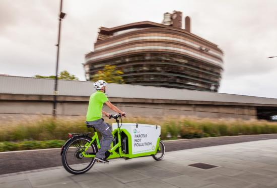 E-cargobike and rider passing in front of Hammersmith's iconic The Ark building