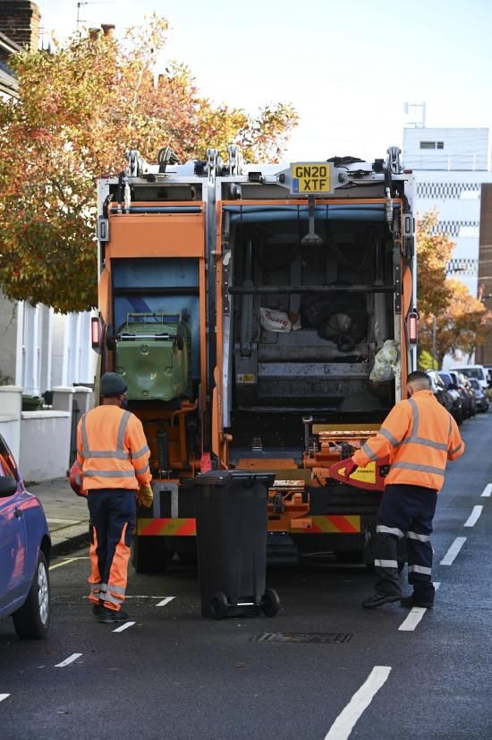 Recycling wheeled bin being emptied into the back of a collection truck by collection operatives