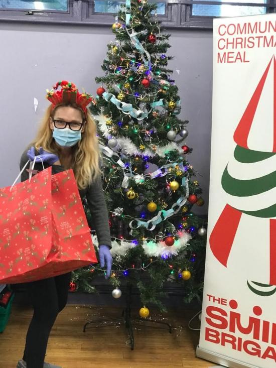 A volunteer wearing face mask and holding a gift bag by a Christmas tree