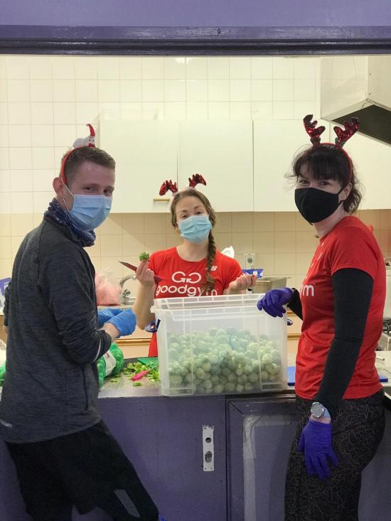 Three people working as volunteers in a kitchen with a large container of Brussel Sprouts