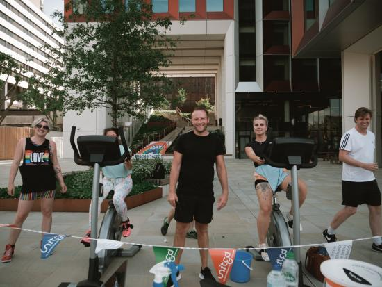 People outside an office building using stationary bikes to fund raise