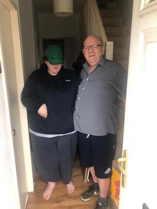 Two people stood inside their front door receiving a food delivery