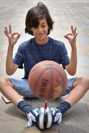 Young boy sitting on the court behind a basketball