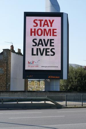 Digital advertising board showing the Stay Home Save Lives message