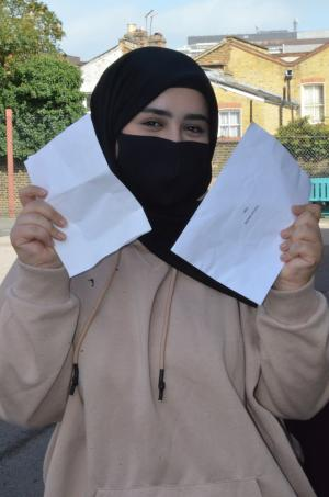 Fatimah M stood outside her school holding her GCSE results