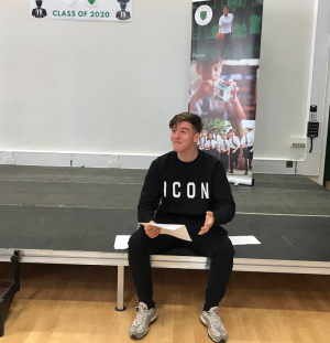 Student from Fulham Cross Academy sitting on the school hall stage smiling